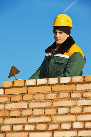 putty: construction mason worker bricklayer installing red brick with trowel putty knife outdoors Stock Photo