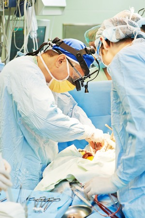 cardiosurgery: Team of surgeon in uniform perform operation on a patient at cardiac surgery clinic. Authentic shooting in challenging conditions