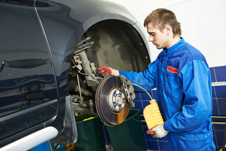 Auto service. car mechanic worker replacing brake liquid of lifted automobile at repair garage shop station