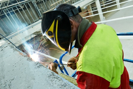 electrode: welder working with electrode at arc welding in construction site