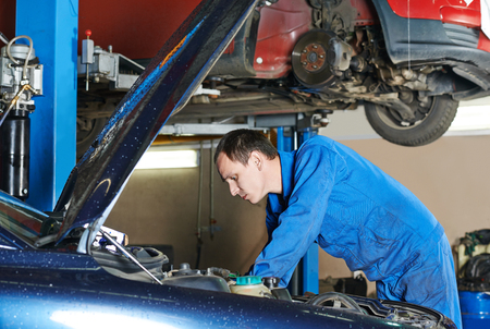 service station: auto mechanic repairman examining automobile car engine at maintenance repair service station garage