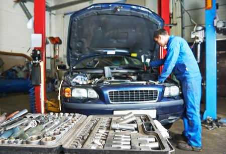 mantenimiento: mecánico de automóviles reparador examinar motor de automóvil en el mantenimiento de reparación de la estación de servicio de garaje