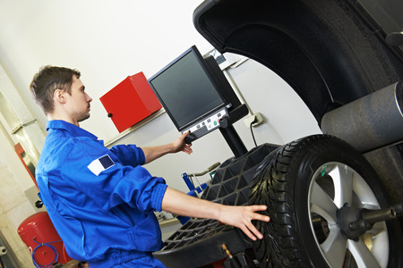 wheel balancing: repair station worker performing computer alignment and balancing of automobile car wheel on special equipment. Focus on machine