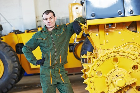 skilled labour: industrial worker during heavy industry machinery bulldozer assembling on production line manufacturing workshop at factory Stock Photo