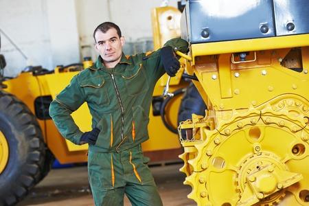 maquinaria pesada: trabajador industrial durante la maquinaria de la industria pesada excavadora montaje en taller de fabricación de la línea de producción en la fábrica Foto de archivo