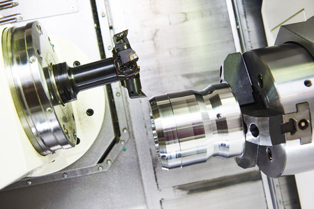 turning operation: metalworking  industry: multi cutting tool pefroming facing cut of metal detail on lathe machine in workshop