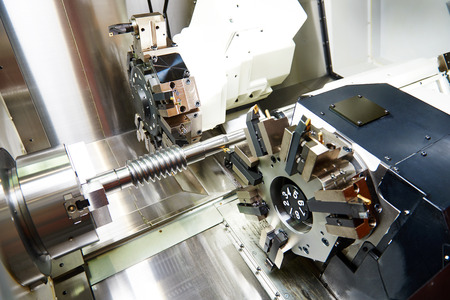 cutting tool: metalworking  industry: cutting tool processing steel metal shaft on lathe machine in workshop Stock Photo