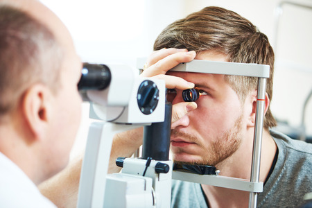 diopter: Ophthalmology concept. Male patient under eye vision examination in eyesight ophthalmological correction clinic Stock Photo