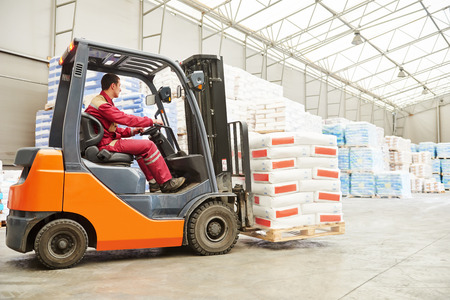 stockpiling: warehousing. Forklift driver stacking pallets with cement packs by stacker loader