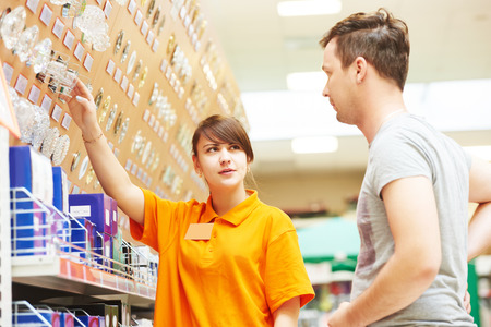 purchaser: Young female assistant seller helps purchaser choosing lamp in hardware shopping mall supermarket