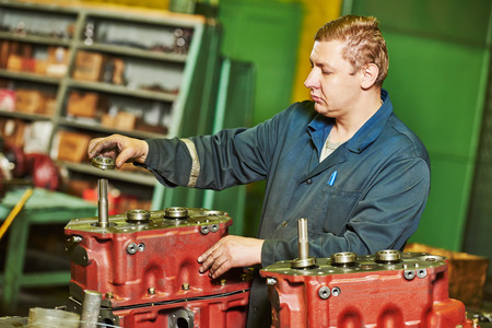 toolroom: industrial worker assembler with gearbox utits at manufacture workshop