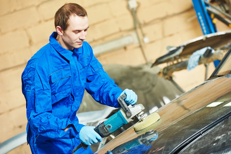 car body: mechanic polishing car body at automobile repair and renew service station shop by power buffer machine Stock Photo