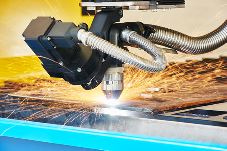 sheet metal: metal working. Plasma or Laser cutting technology of flat sheet metal steel material with sparks Stock Photo