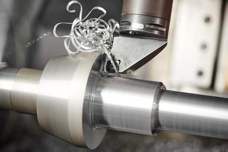 metaalverwerkende industrie: het snijden van staal metalen as bewerking op draaibank machine in de werkplaats. Selectieve aandacht op het gereedschap