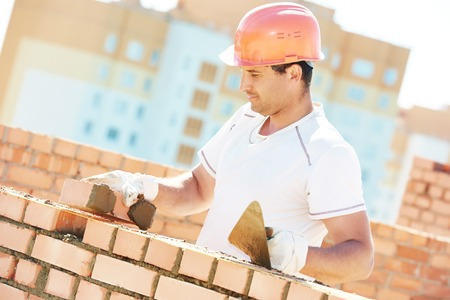 sand lime bricks: construction worker. mason bricklayer installing red brick with trowel putty knife outdoors