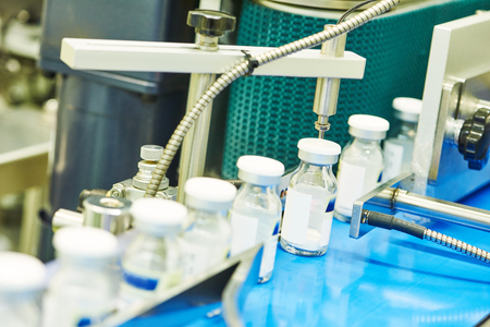 pharmaceutical industry. Production line machine conveyor at factory with bottles Stock Photo