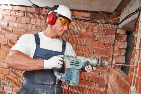 Builder munkás pneumatikus ütvefúró lyukasztó gépek készítés lyuk fal építkezésen