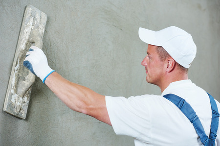plasterer: Plasterer at indoor wall renovation decoration with float and plaster Stock Photo