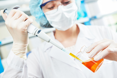 science scientific: science laboratory work. female scientific researcher or doctor holding flask with pink liquid solution
