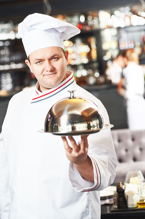 servings: portrait of male cook chef at restaurant serving food with cloche lid