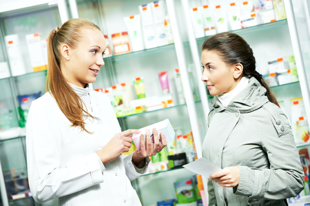 pharmacist chemist woman helps to choose medicine for young to female buyer in pharmacy drugstore photo