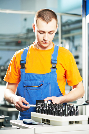mechanical industrial worker measuring detail near metalwork machining center in tool manufacture workshop. Focus on labor face