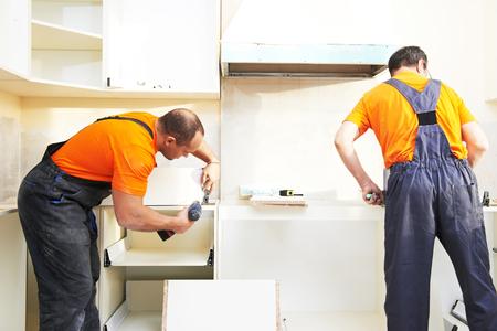 marking up: Craftsman kitchen carpenter workers at kitchen furniture set installation service work