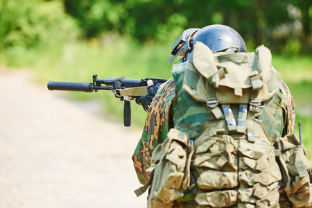 assault: military. soldier with assault rifle in uniform patrolling territory outdoors Stock Photo