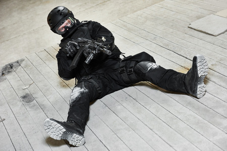 cleanup: Military industry. Special forces or anti-terrorist police soldier,  private military contractor armed with pistol ready to attack lying on ground during clean-up operation, mission Stock Photo