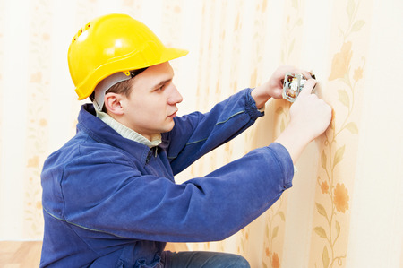 light switch: electrician worker installing and light switch or power wall outlet socket