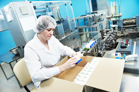 manufacture: pharmaceutical factory worker at pharmacy industry manufacture packing medicine into boxes Stock Photo
