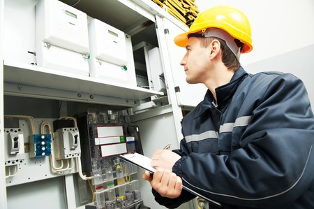 electrician builder engineer inspector checking data of equipment in fuse box Stock Photo - 58661764