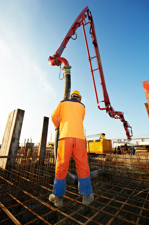 concrete construction: builder worker with boom pump pouring concrete on metal rods reinforcement of formwork