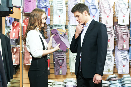 choosing: Young man choosing shirt and necktie during apparel shopping at clothing store