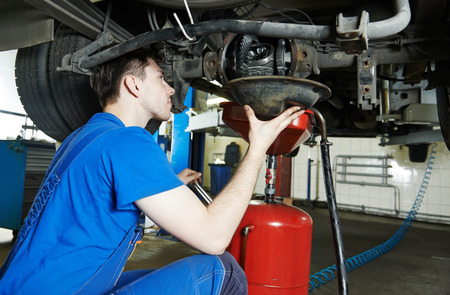 scheduled replacement: auto repairman mechanic works with rear axle reduction gear of commercial van in car auto repair or maintenance shop service station