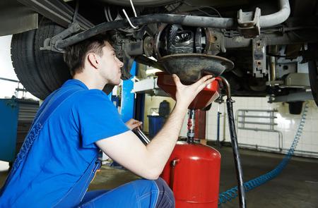 auto reparateur mechanic werkt met achteras reductie versnellingsbak van de bedrijfswagen in de auto auto reparatie of onderhoud winkel tankstation