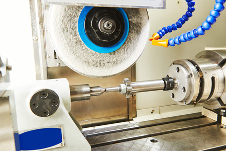 dimond: metalworking  industry. polishing and finishing grinding machine with metal cogwheel gera in workshop.