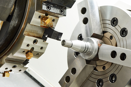 milling center: metalworking  industry. cutting process of steel metal shaft on turning lathe machine in workshop. Stock Photo