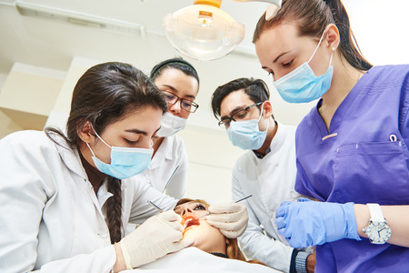Dentistry education. Female dentist doctor teacher explaining treatment procedure to iranian asian students group in dental clinic Stock Photo
