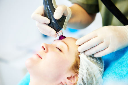 procedures: Young woman under forehead laser therapy cosmetology procedure