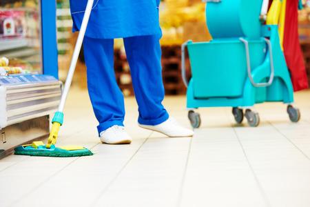 mujer limpiando: Hombre trabajador de limpia en uniforme con la fregona limpia el suelo de la tienda de supermercado tienda
