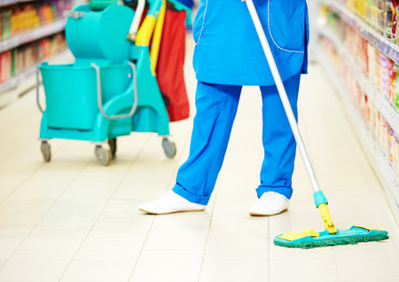 Female cleaner worker in uniform  with mop cleaning the floor of supermarket shop store Foto de archivo