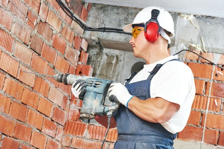 building tool: Builder worker with pneumatic hammer drill perforator equipment making hole in wall at construction site Stock Photo