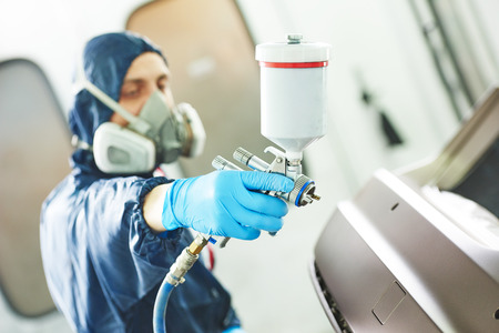 priming paint: Close-up of spray gun using by mechanic worker during painting auto car bumper in a paint chamber