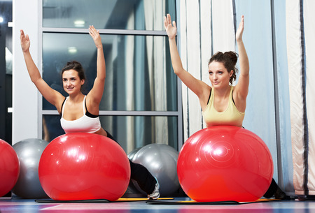 woman with fitness ball in gym at physical training in sport wear