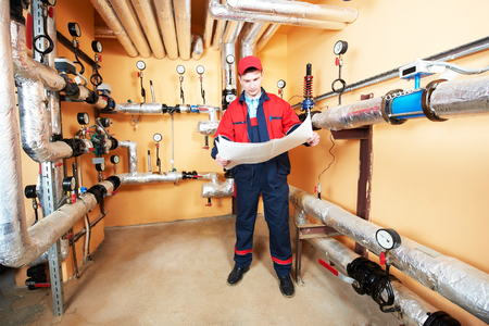 esquema: ingeniero reparador de mantenimiento de equipos de sistema de calefacción en una casa de calderas Foto de archivo
