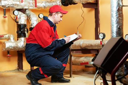 plumber: ingeniero reparador de mantenimiento de equipos de sistema de calefacción en una casa de calderas Foto de archivo