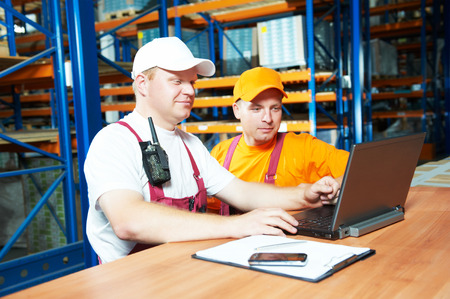 two young workers man in uniform in front of warehouse rack arrangement stillages using notebook laptop computer photo