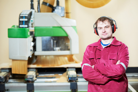 Portrait of industrial carpenter worker operating wood cutting machine during wooden door furniture manufacturing photo