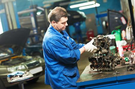 mecanico: trabajador mecánico automotriz trabaja con el motor o la caja de cambios durante el mantenimiento de automóvil en la estación de servicio de reparación